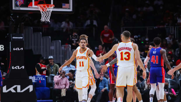 Atlanta Hawks guard Trae Young (11) high fives guard Bogdan Bogdanovic (13) during the first quarter against the Detroit Pistons at State Farm Arena.