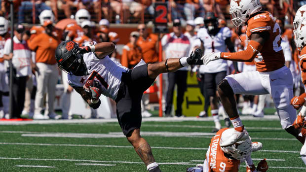Oct 16, 2021; Austin, Texas, USA; Oklahoma State Cowboys running back Jaylen Warren (7) leaps over Texas Longhorns defensive back Josh Thompson (9) in the second half at Darrell K Royal-Texas Memorial Stadium.