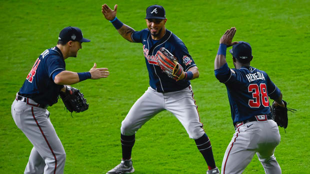 Atlanta Braves center fielder Adam Duvall (14) and left fielder Eddie Rosario (8) and center fielder Guillermo Heredia (38) celebrate the win over the Houston Astros in game one of the 2021 World Series.