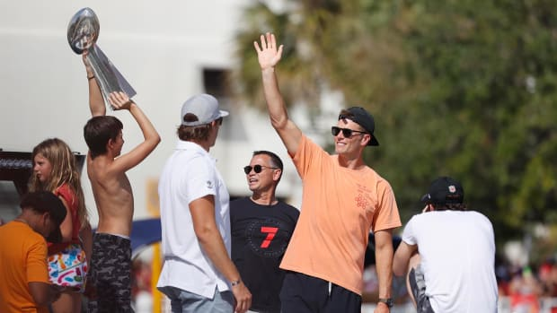 Feb 10, 2021; Tampa Bay, FL, USA; Tampa Bay Buccaneers quarterback Tom Brady waves to the crowd as son Benjamin hoists the Vince Lombardi Trophy during a boat parade to celebrate victory in Super Bowl LV against the Kansas City Chiefs.