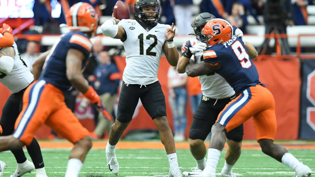 Nov 30, 2019; Syracuse, NY, USA; Wake Forest Demon Deacons quarterback Jamie Newman (12) passes the ball as Syracuse Orange defensive back Evan Foster (9) pressures during the first quarter at the Carrier Dome. Mandatory Credit: Rich Barnes-USA TODAY Sports
