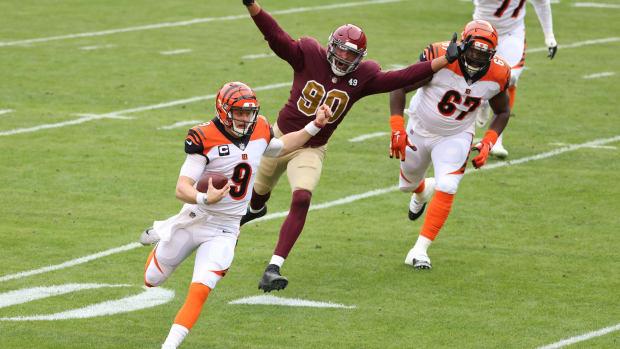 Nov 22, 2020; Landover, Maryland, USA; Cincinnati Bengals quarterback Joe Burrow (9) runs with the ball as Washington Football Team defensive end Montez Sweat (90) chases in the second quarter at FedExField. Mandatory Credit: Geoff Burke-USA TODAY Sports