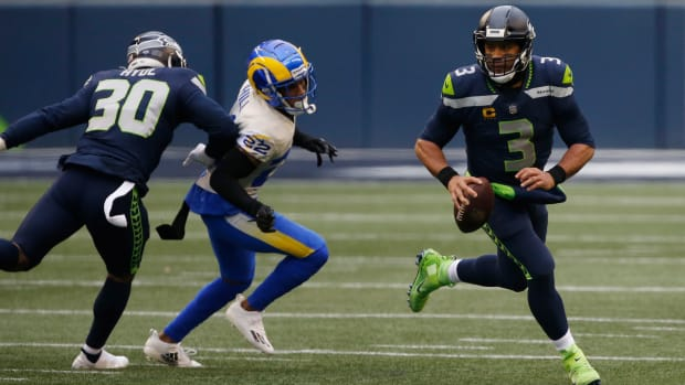 Jan 9, 2021; Seattle, Washington, USA; Seattle Seahawks quarterback Russell Wilson (3) rolls out of the pocket while pressured by Los Angeles Rams cornerback Troy Hill (22) during the second quarter at Lumen Field.
