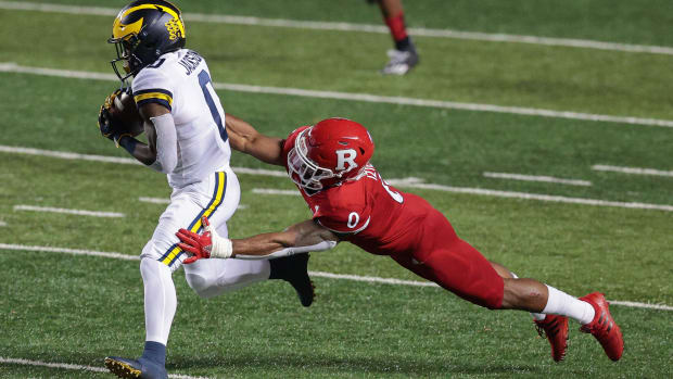 Nov 21, 2020; Piscataway, New Jersey, USA; Michigan Wolverines wide receiver Giles Jackson (left) carries the ball against Rutgers Scarlet Knights defensive back Christian Izien (right) during the first half at SHI Stadium. Mandatory Credit: Vincent Carchietta-USA TODAY Sports