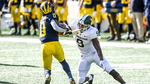 Michigan State's Dominique Long, right, tackles Michigan's Giles Jackson during the second quarter on Saturday, Oct. 31, 2020, at Michigan Stadium in Ann Arbor. 201031 Msu Um 082a