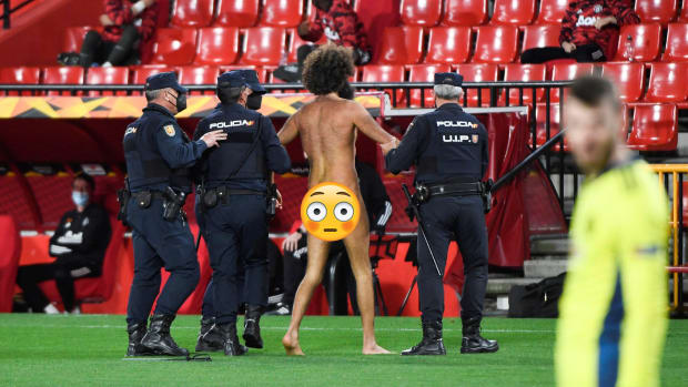 A streaker is escorted off the pitch during Manchester United-Granada