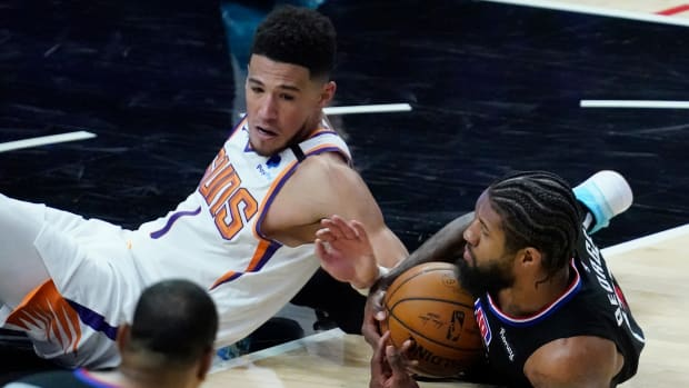 Apr 8, 2021; Los Angeles, California, USA; LA Clippers guard Paul George (13) goes to the floor to pick up a loose ball away from Phoenix Suns guard Devin Booker (1) during the third quarter at Staples Center. Mandatory Credit: Robert Hanashiro-USA TODAY Sports