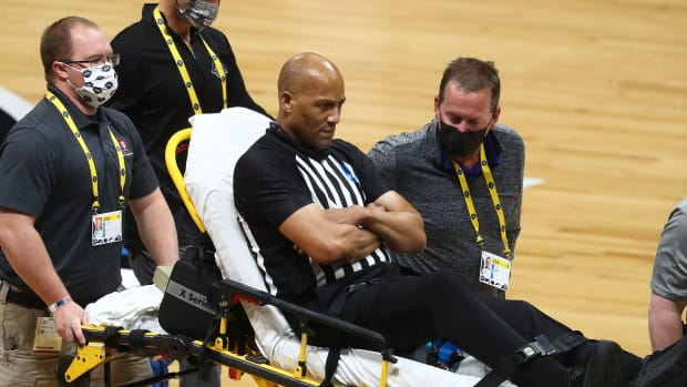 Referee Bert Smith is carted off the court in the Elite Eight