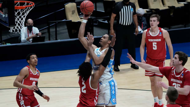 Mar 19, 2021; West Lafayette, Indiana, USA; North Carolina Tar Heels forward Garrison Brooks (middle) shoots the ball over Wisconsin Badgers forward Aleem Ford (2) during the first half in the first round of the 2021 NCAA Tournament at Mackey Arena.