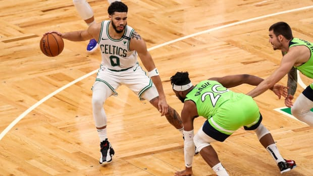 Apr 9, 2021; Boston, Massachusetts, USA; Boston Celtics forward Jayson Tatum (0) dribbles down the court defended by Minnesota Timberwolves forward Josh Okogie (20) during the second half at TD Garden.