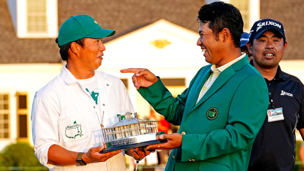 Hideki Matsuyama celebrates with his caddie Shota Hayafuji and The Master trophy.