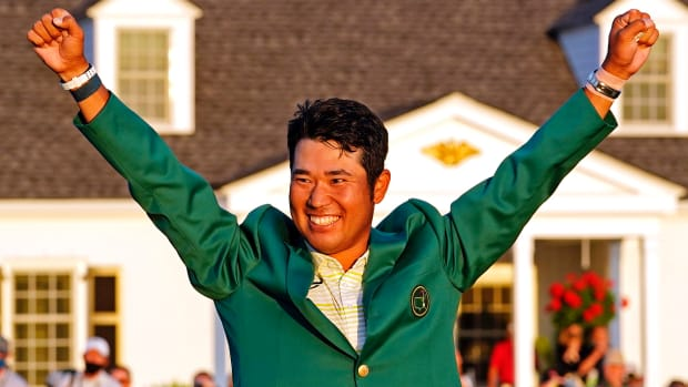 Hideki Matsuyama celebrates with the green jacket after winning the Masters golf tournament.