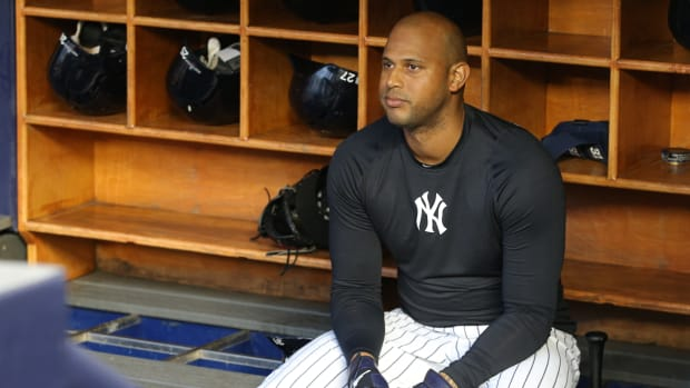 Yankees' Aaron Hicks sits on a bench in the dugout