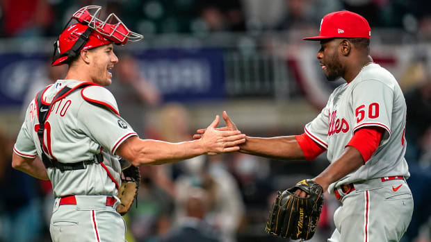 Phillies relief pitcher Hector Neris celebrates with catcher J.T. Realmuto after beating the Braves