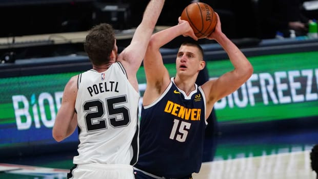 Spurs center Jakob Poeltl trying to defend Nuggets center Nikola Jokić