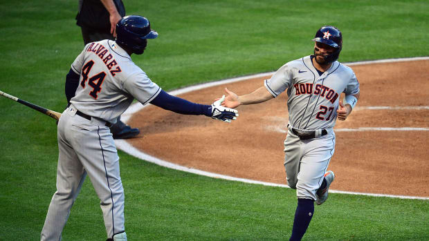 Jose Altuve (27) is greeted by left fielder Yordan Alvarez (44)