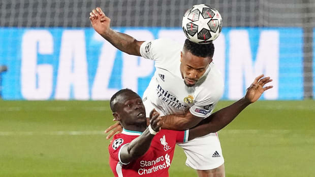Real Madrid's Eder Militao heads the ball away from Liverpool's Sadio Mane