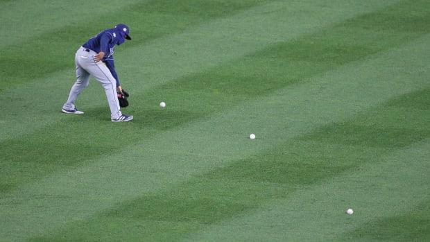 Rays picking up baseballs thrown on field by Yankees fans