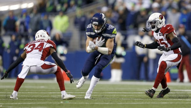 Seattle Seahawks tight end Jacob Hollister (48) runs for yards after the catch before being tackled by Arizona Cardinals strong safety Jalen Thompson (34) and defensive back Chris Jones (25) during the fourth quarter at CenturyLink Field.