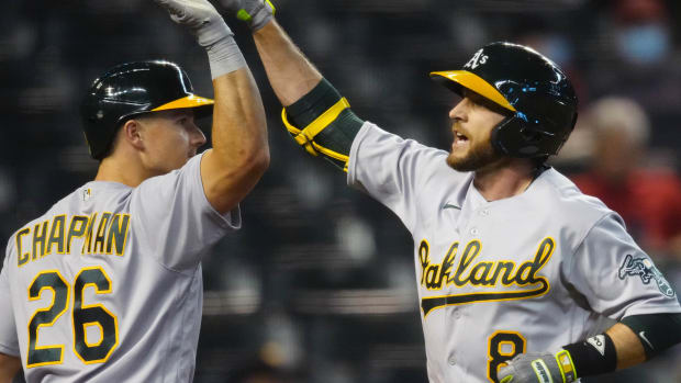 Matt Chapman and Jed Lowrie celebrate a run scored.