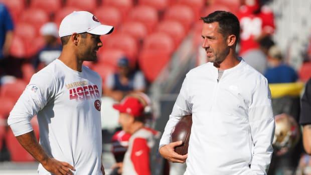 49ers head coach Kyle Shanahan speaks to quarterback Jimmy Garoppolo on the field