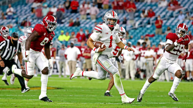 Jan 11, 2021; Miami Gardens, Florida, USA; Ohio State Buckeyes quarterback Justin Fields (1) runs the ball against Alabama Crimson Tide linebacker Christian Harris (8) and defensive back DeMarcco Hellams (29) during the third quarter in the 2021 College Football Playoff National Championship Game.
