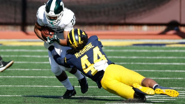 Michigan State Spartans running back Jordon Simmons (22) is tackled by DUPLICATE***Michigan Wolverines defensive back Joshua Luther (44)***Michigan Wolverines linebacker Cameron McGrone (44) in the first half at Michigan Stadium.