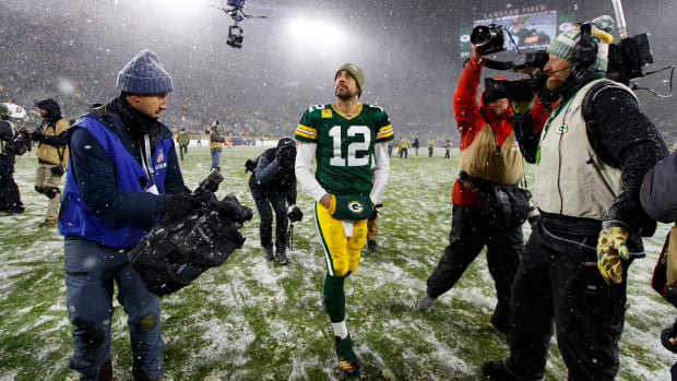 Aaron Rodgers walks off Lambeau Field in the snow with cameras pointed at him