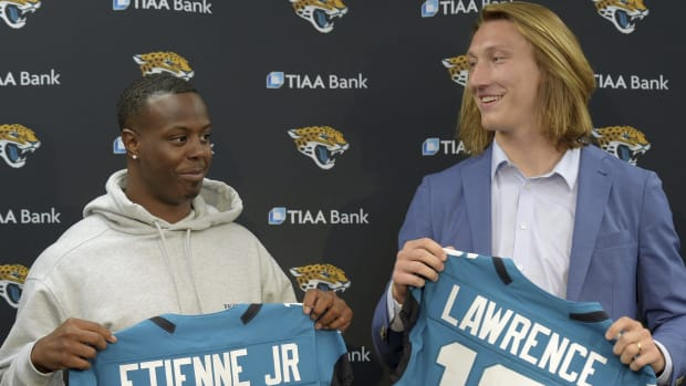 Former Clemson teammates Travis Etienne and Trevor Lawrence and now Jacksonville Jaguars teammates with their new jerseys during an introductory press conference Friday, April 30, 2021