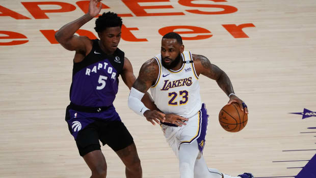 Lakers forward LeBron James and Raptors forward Stanley Johnson on the court