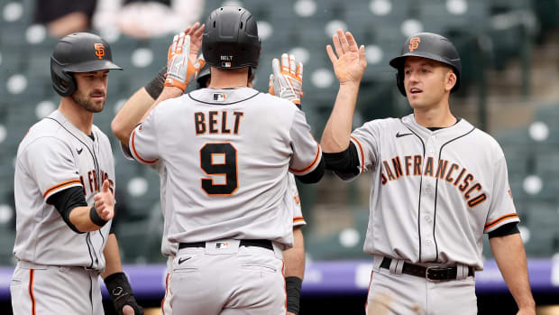 Brandon Belt celebrates after hitting a grand slam in the first inning against the Rockies