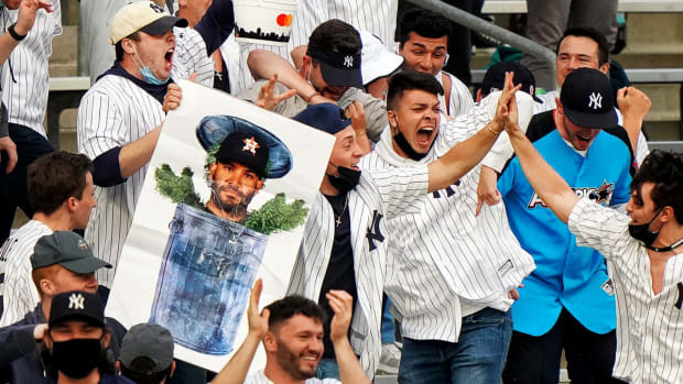 Yankees fans celebrate with a poster of José Altuve as Oscar the Grouch.