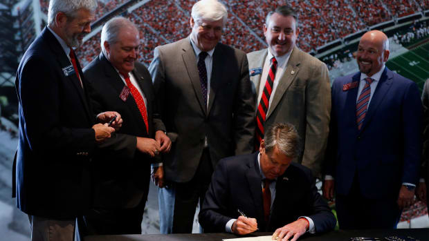 Georgia Governor Brian Kemp signs House Bill 617 which will allow student athletes to control and earn money off of their name, image, and likeness at Sanford Stadium in Athens, Ga., on Thursday, May 6, 2021.