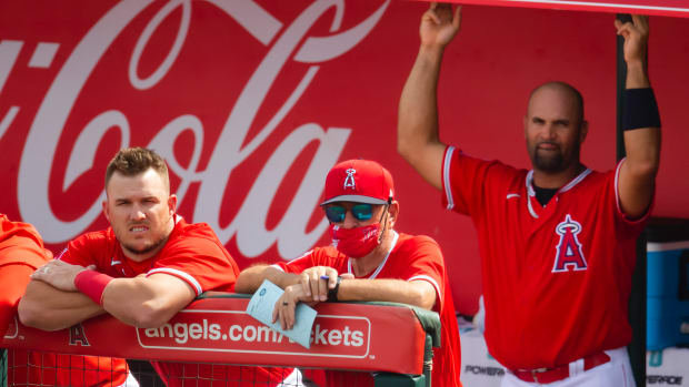 Los Angeles Angels outfielder Mike Trout (left) with manager Joe Maddon (center) and first baseman Albert Pujols against the Seattle Mariners during a Spring Training game at Tempe Diablo Stadium.