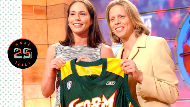 Sue Bird holding up a Seattle Storm jersey
