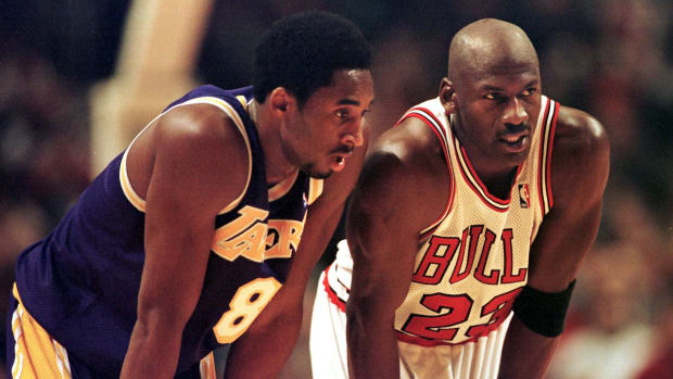 Kobe Bryant and Michael Jordan stand side by side during an NBA game