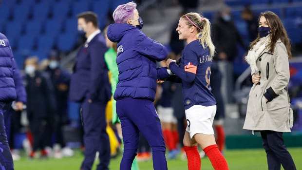 Megan Rapinoe and Eugénie Le Sommer embrace.
