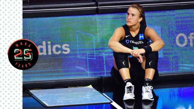 Sabrina Ionescu sitting on the court, looking pensive