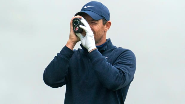 Golfer Rory McIlroy holding a range finder
