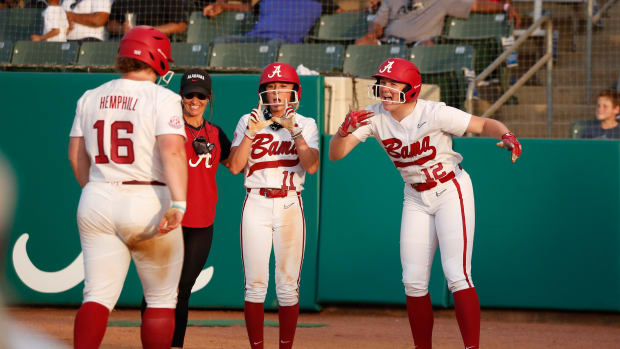 Bailey Hemphill is met at home plate by Alexis Mack and Kaylee Tow