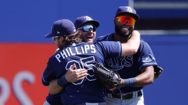 Tampa Bay Rays right fielder Brett Phillips (35), Tampa Bay Rays center fielder Kevin Kiermaier (39) and Tampa Bay Rays right fielder Manuel Margot (13) hug