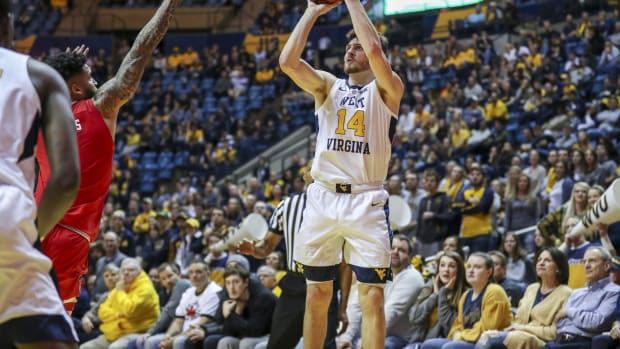 Jan 2, 2019; Morgantown, WV, USA; West Virginia Mountaineers guard Chase Harler (14) shoots a three pointer during the second half against the Texas Tech Red Raiders at WVU Coliseum.
