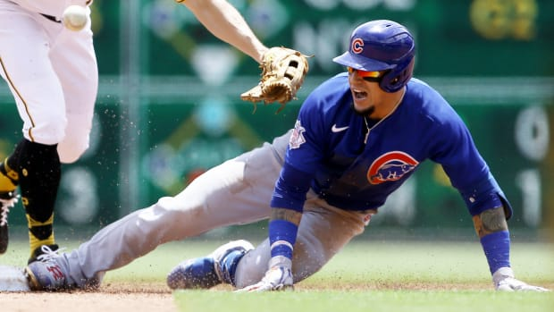 May 27, 2021; Pittsburgh, Pennsylvania, USA;  Chicago Cubs shortstop Javier Baez (9) is safe at second base after a prolonged run down and an error as Pittsburgh Pirates center fielder Bryan Reynolds (10) can not handle the throw during the third inning at PNC Park.