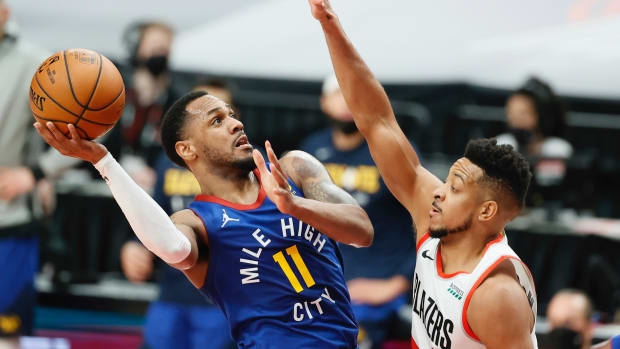 Denver Nuggets point guard Monte Morris (11) shoots the ball against Portland Trail Blazers shooting guard CJ McCollum (3) during the first half of Game 3 in the first round.