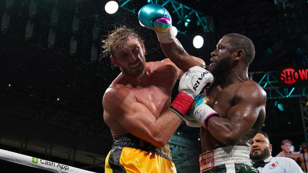 Floyd Mayweather Jr. (Green Trunks) fights Logan Paul (Yellow Trunks) during an exhibition boxing match at Hard Rock Stadium.