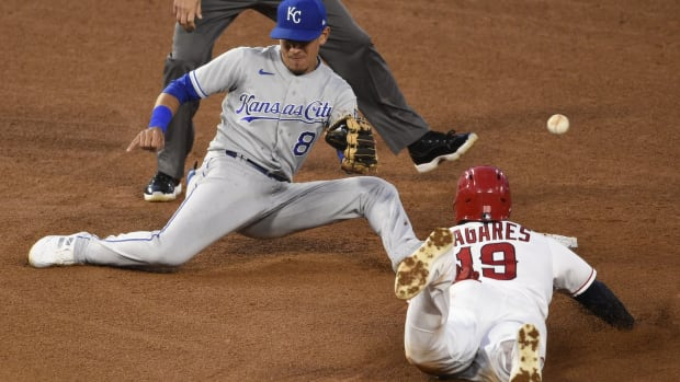 Jun 7, 2021; Anaheim, California, USA; Kansas City Royals shortstop Nicky Lopez (8) is unable to catch the ball while Los Angeles Angels center fielder Juan Lagares (19) steals second base during the fourth inning at Angel Stadium. Mandatory Credit: Kelvin Kuo-USA TODAY Sports