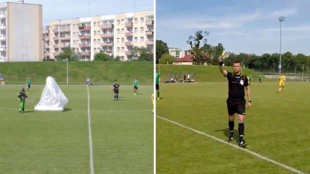 Skydiver lands on field during Polish soccer game