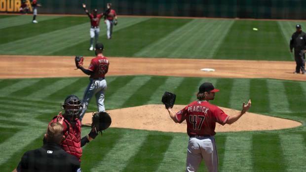 Arizona Diamondbacks starting pitcher Matt Peacock (47) reacts to a safe call by umpires after center fielder Ketel Marte appeared to catch a deep fly ball by Oakland Athletics center fielder Mark Canha.