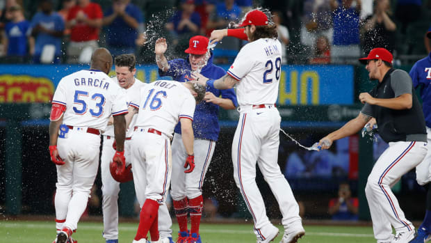 Jun 9, 2021; Arlington, Texas, USA; Texas Rangers third baseman Brock Holt (16) is congratulated by his teammates after driving in the winning run in the eleventh inning against the San Francisco Giants at Globe Life Field.
