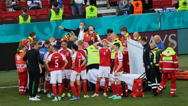 Denmark surrounds Christian Eriksen after he collapses on the field at Euro 2020.